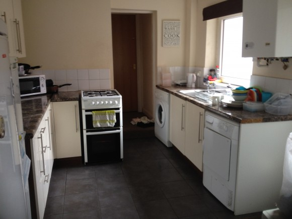 This kitchen area features a washing machine, tumble drier, fridge freeze units, a microwave, gas cooker, sink and draining area, and designated cabinets for each tennant.